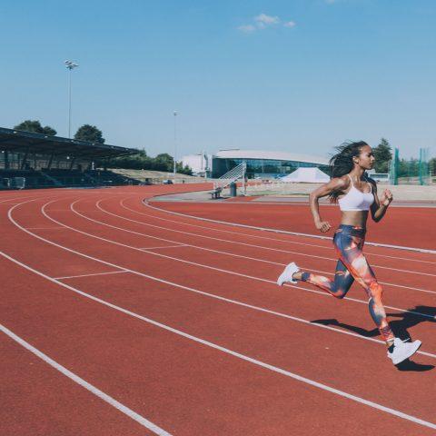 Kvinna springer på löpbana